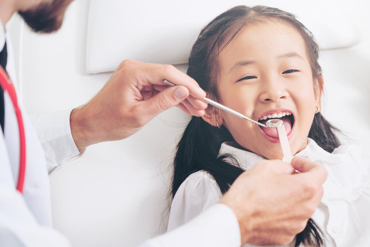 dentist cleaning young girl's teeth